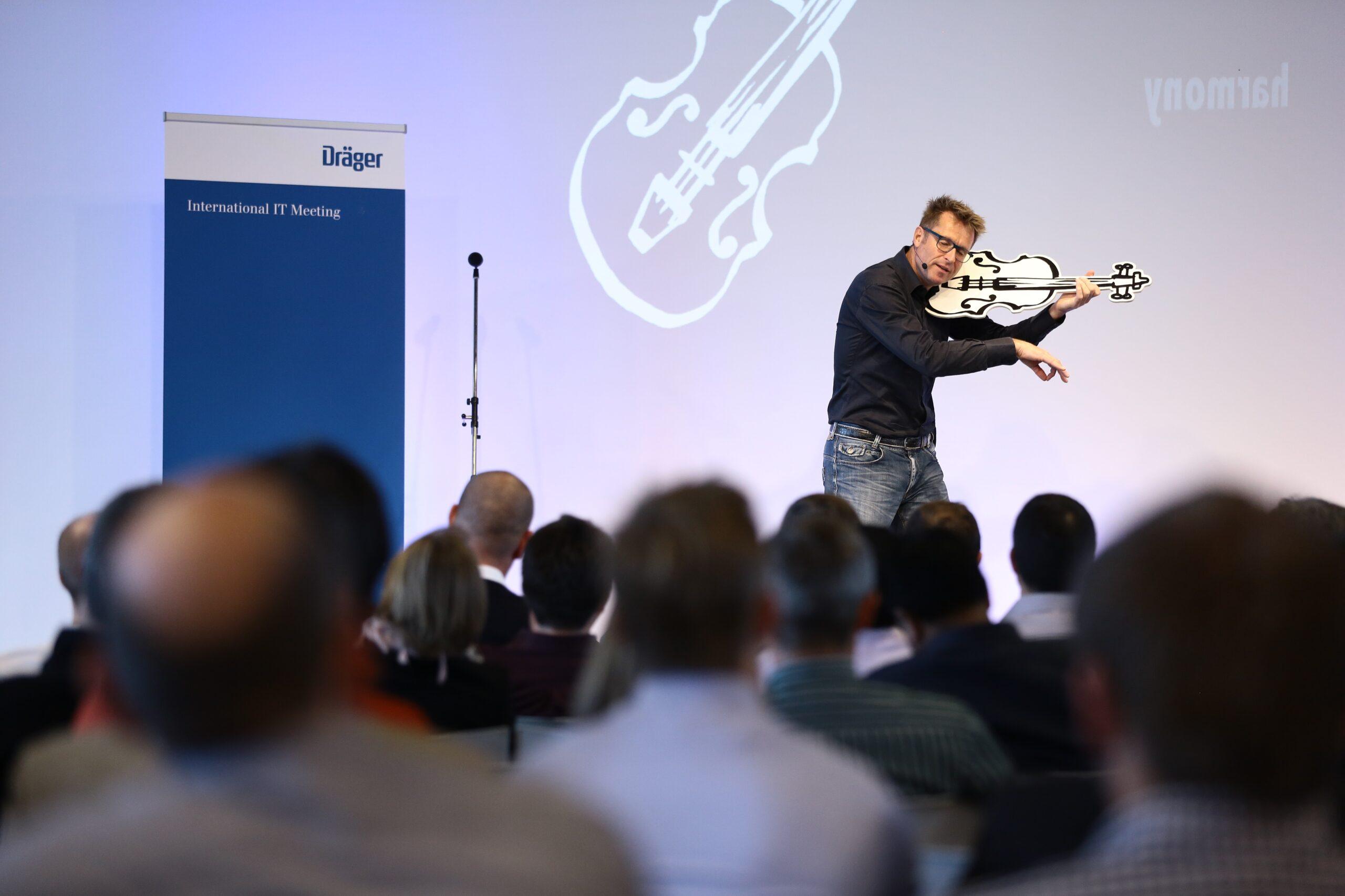 Richard de hoop op het podium met viool sprekend over veerkracht